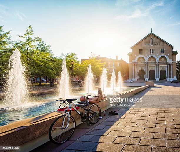 Cyclist resting next to fountains at Montreal parc des faubourgs