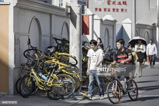 A cyclist rides a BeijingMobikeTechnology Co bicycle past a pile of other ridesharing bikes in Shanghai China on Thursday Sept 12 2017 Across...