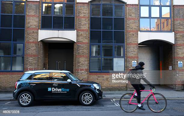 A cyclist rides a bicycle past a Mini Countryman automobile part of the DriveNow carsharing venture between Bayerische Motoren Werke AG and Sixt SE...
