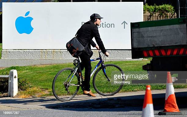 A cyclist rides a bicycle past a sign at Apple Inc's campus in Cork Ireland on Tuesday June 4 2013 Speaking to lawmakers in Dublin last month Irish...