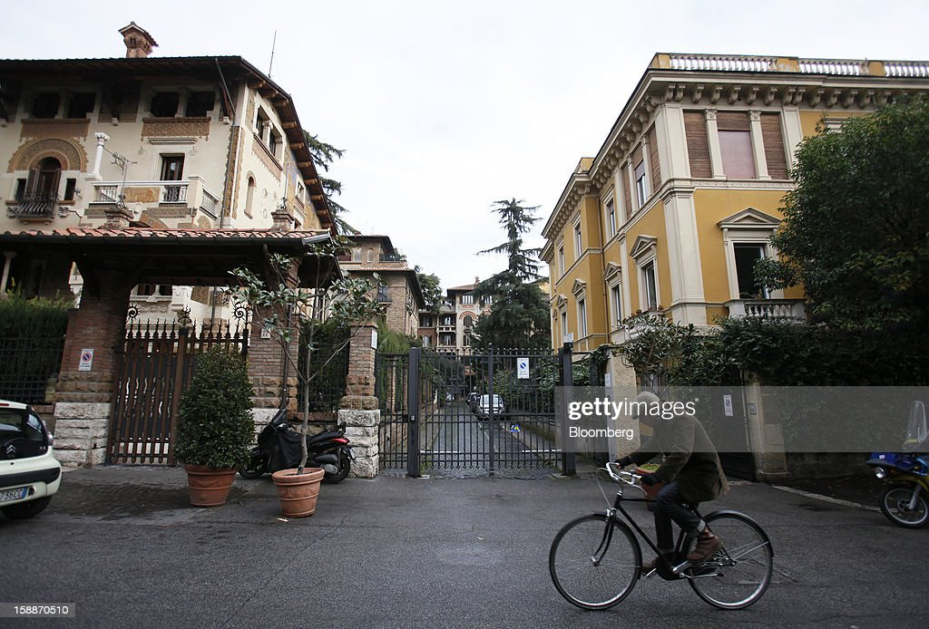 A cyclist rides a bicycle past the gates to a private residential street in the Coppede district of Rome, Italy, on Wednesday, Jan. 2, 2013. Italian property sales often are reported to be less than the actual price paid to reduce taxes or skirt controls on money laundering, according to the website of the finance police, which reports to Italian Finance Minister Vittorio Grilli. Photographer: Alessia Pierdomenico/Bloomberg via Getty Images