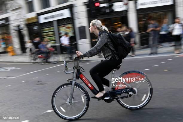 A cyclist rides a hired bicycle displaying logos of sponsor Banco Santander SA in London UK on Tuesday Aug 15 2017 Banco Santander Spains biggest...