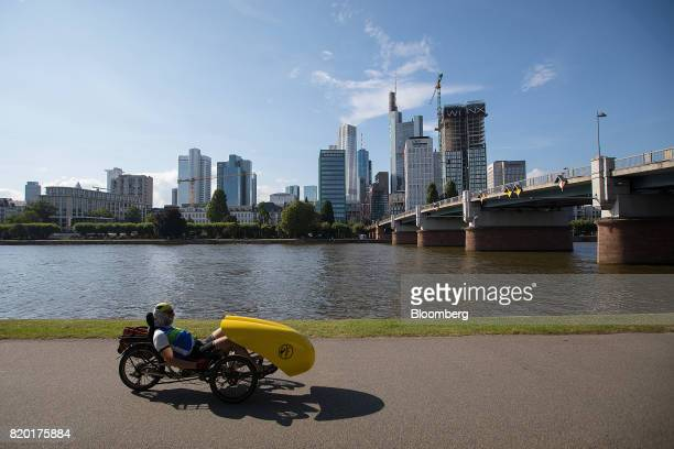 A cyclist rides a recumbent bicycle alongside the River Main as skyscrapers stand beyond in Frankfurt Germany on Thursday July 20 2017 Frankfurt has...