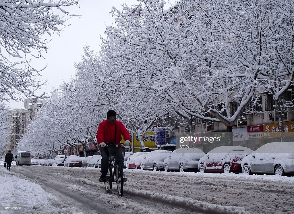 A cyclist rides along a snow-covered road on February 19, 2013 in Nanjing, China. Heavy snow hit large areas of east China on Tuesday.