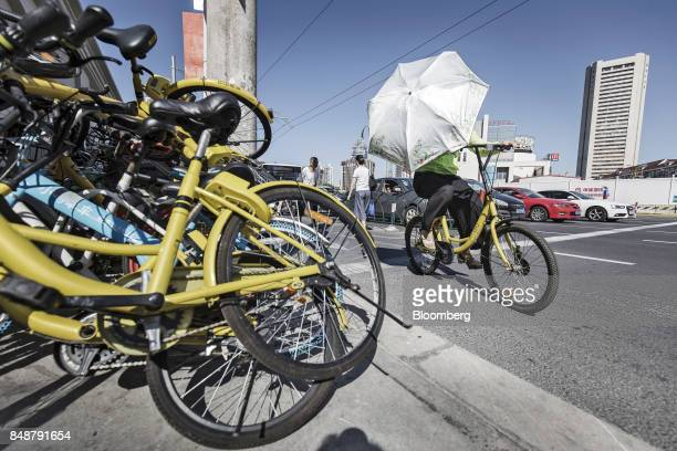A cyclist rides an Ofo Inc bicycle past a pile of other ridesharing bikes in Shanghai China on Thursday Sept 12 2017 Across Chinese cities sidewalks...