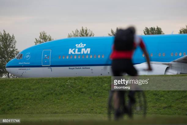 A cyclist rides as a KLM passenger plane operated by the Dutch arm of Air FranceKLM Group stands at Schiphol airport in Amsterdam Netherlands on...