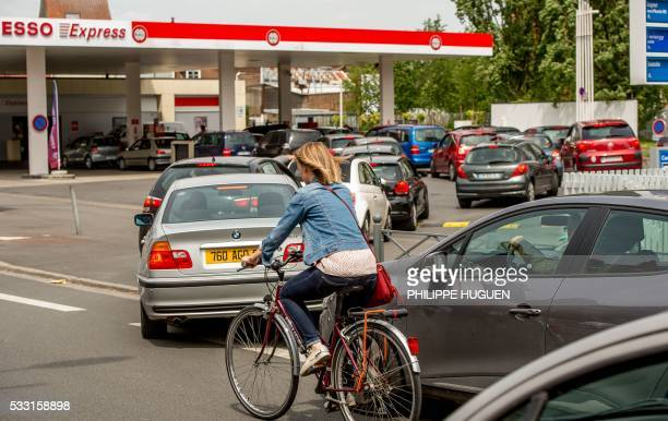 A cyclist rides as people in their car queue on line at a gas station on May 21 2016 in Lille northern France following the blockades of several oil...
