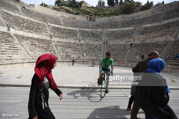 A cyclist rides at the ancient Roman theatre in the centre of Amman during a welcome ceremony for members of the Middle East Peace Tour preEvent on...