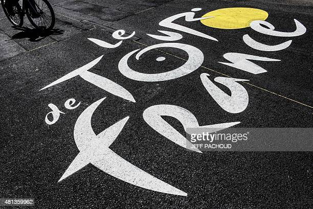 A cyclist rides beside The Tour de France logo near the finish line during the 1905 km seventh stage of the 102nd edition of the Tour de France...
