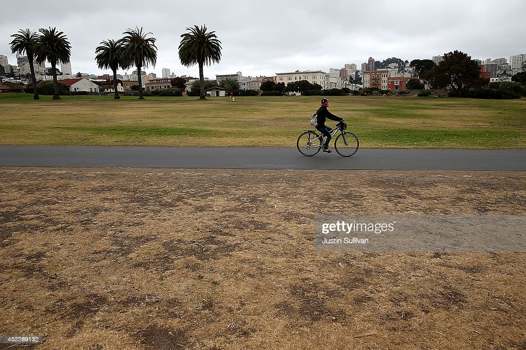 A cyclist rides by dead grass at the Fort Mason Great Meadow on July 17, 2014 in San Francisco, California. As the severe drought in California contiues to worsen, the State's landscape and many resident's lawns are turning brown due to lack of rain and the discontinuation of watering.