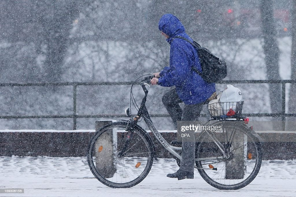 A cyclist rides during a snowfall on January 11, 2013 in Luebeck, northern Germnay.