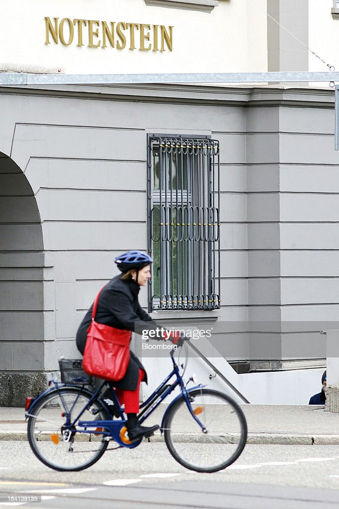 A cyclist rides her bicycle past the headquarters of Notenstein Privatbank AG, formerly the headquarters of Wegelin & Co., in St. Gallen, Switzerland, on Wednesday, March 20, 2013. Wegelin & Co., who sold Notenstein Privatbank AG to Raiffeisen Group last year, were ordered to pay U.S. authorities almost $58 million at the end of a criminal case after the Swiss bank pleaded guilty to helping American taxpayers hide more than $1.2 billion from the Internal Revenue Service. Photographer: Gianluca Colla/Bloomberg via Getty Images