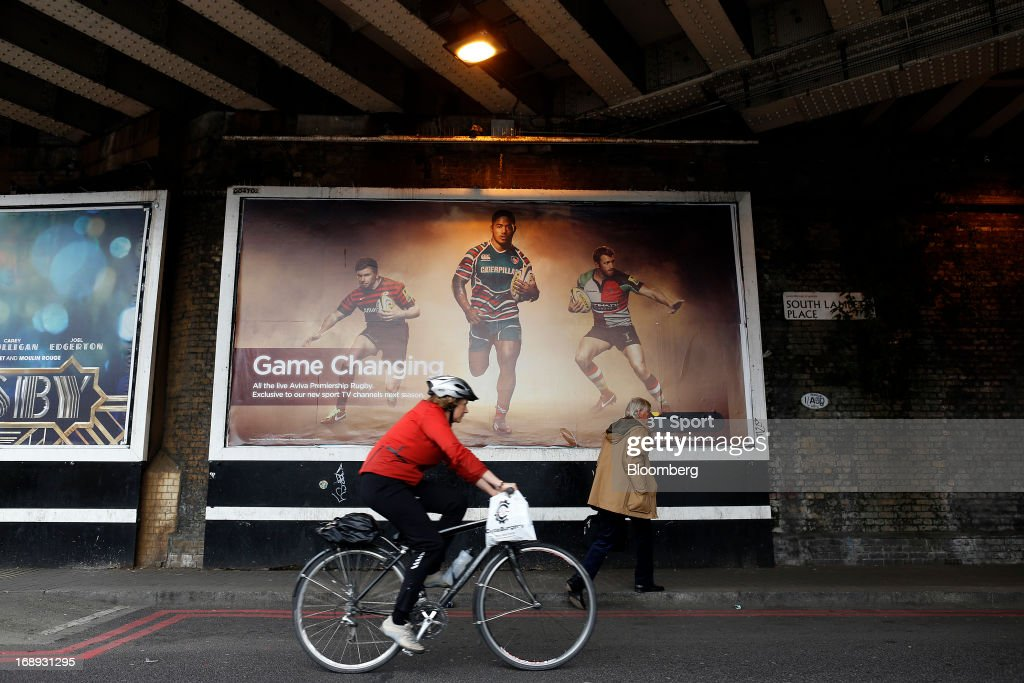 A cyclist rides her bike past a billboard advertisement for BT Group Plc's new sports television service BT Sport in London, U.K. on Friday, May 17, 2013. BT Group Plc said it will offer its new BT Sport channels free with broadband subscriptions to make its bundles of phone, Internet and TV service more appealing. Photographer: Simon Dawson/Bloomberg via Getty Images