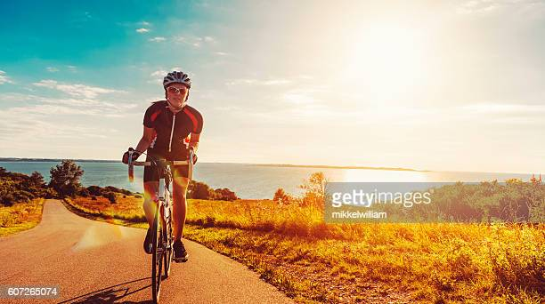 Cyclist rides her bike up a steep hill at sunset