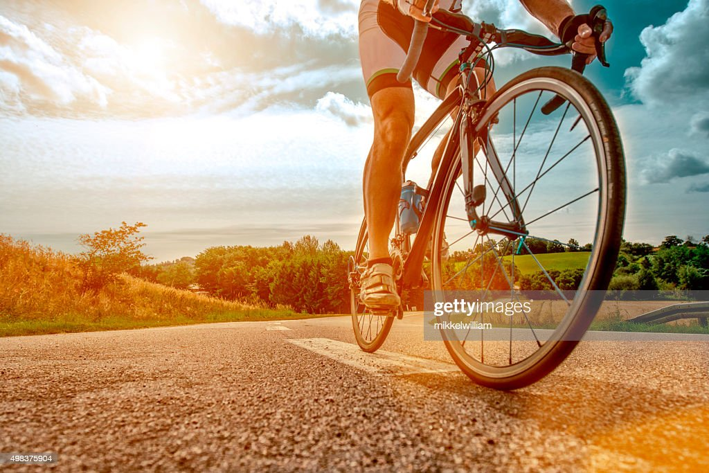 Cyclist rides his bike up a steep hill : Stock Photo