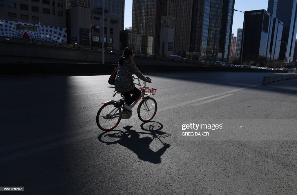 A cyclist rides on a street in Beijing on March 14, 2017. China retail sales growth decelerated to 9.5 percent year-on-year in January and February, government data showed on March 14, as policymakers work to keep the world's second-largest economy on a stable growth path. /