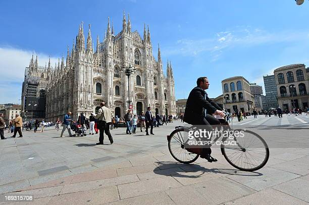 A cyclist rides on piazza del Duomo in Milan on May 22 2013 AFP PHOTO / GIUSEPPE CACACE