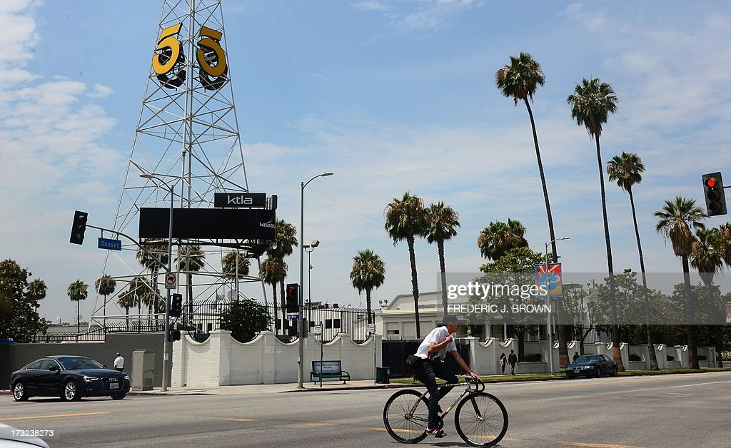 A cyclist rides on Sunset Boulevard past the KTLA channel 5 tower in Hollywood, California on July 10, 2013. The Tribune Company, a group which owns 23 television stations including KTLA, announced plans Wednesday to spin off its newspaper division, which includes the Los Angeles Times and Chicago Tribune, separating the struggling unit from its growing television station holdings. Tribune Company last week announced a $2.7 billion deal to buy 19 more local television stations and has said splitting into two distinct companies would give each 'greater financial and operational focus.' AFP PHOTO/Frederic J. BROWN