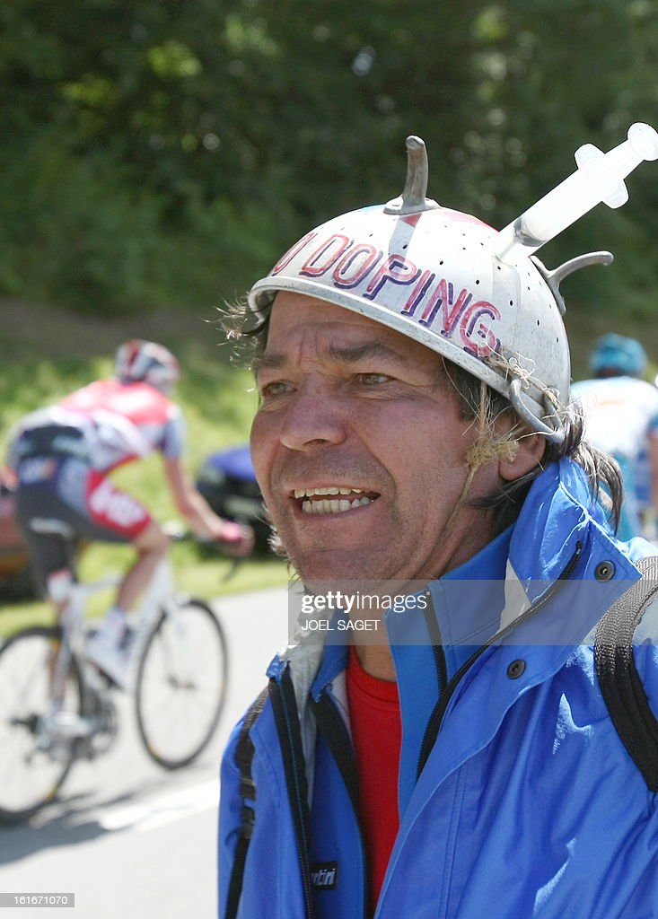 A cyclist rides pas a fan holding wearing a helmet with a syringe mounted on it to denounce cycling doping on July 19, 2009 in the 207,5 km and fifteenth stage of the 2009 Tour de France cycling race run between Pontarlier and Verbier (Switzerland).