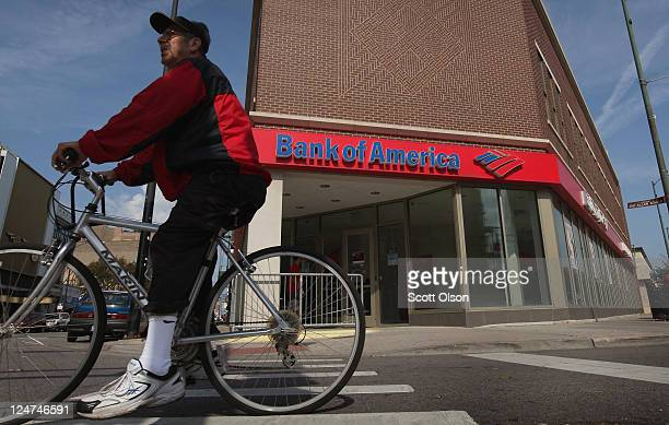 A cyclist rides past a Bank of America branch on September 12 2011 in Chicago Illinois Bank of America in an attempt to reduce expenses by $5 billion...