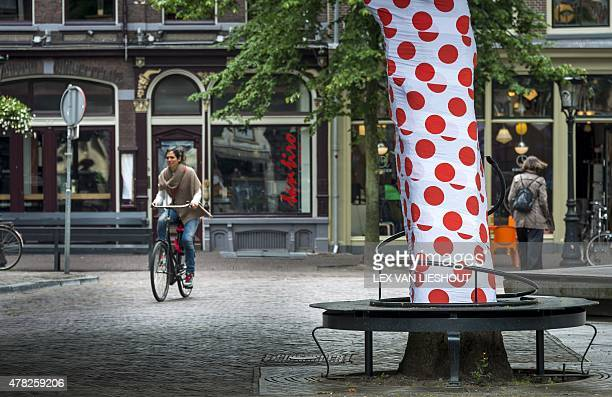 A cyclist rides past a decorated tree in Utrecht on June 24 2015 as preparations for the Grand Depart of the Tour De France get underway across the...