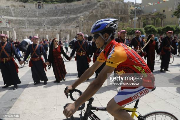 A cyclist rides past a group of traditional dancers at the ancient Roman theatre in the centre of Amman during a welcome ceremony for members of the...