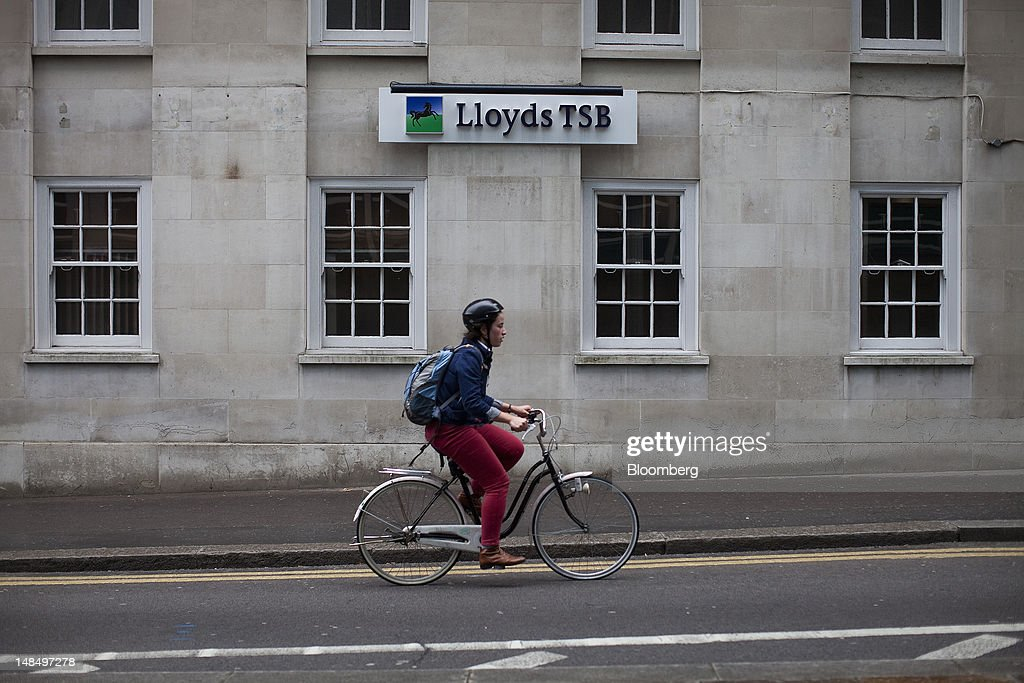 A cyclist rides past a Lloyds TSB bank branch, part of the Lloyds Banking Group Plc, in London, U.K., on Wednesday, July 18, 2012. The U.K. financial regulator said it's investigating seven lenders over attempts to manipulate interbank offered rates as lawmakers criticized it for not opening the probe earlier. Photographer: Simon Dawson/Bloomberg via Getty Images