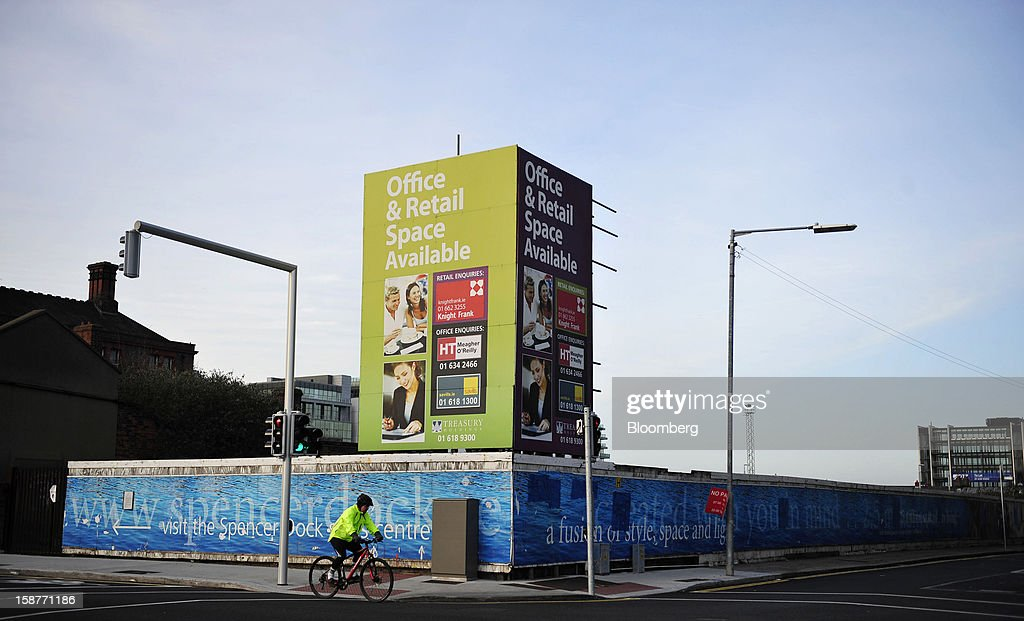 A cyclist rides past a sign advertising commercial office space and retail outlets at a stalled development site near in the Docklands area of Dublin, Ireland, on Thursday, Dec. 27, 2012. Ireland will take over the EU presidency in January as the euro-area wrestles with putting the European Central Bank in charge of lenders within the currency union and other participating nations. Photographer: Aidan Crawley/Bloomberg via Getty Images