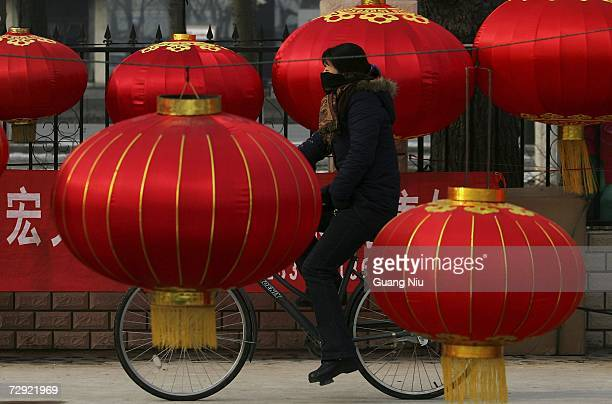 A cyclist rides past an outdoor market on January 4 2007 in Beijing China China's economy will slow a bit this year due to high prices for oil and...