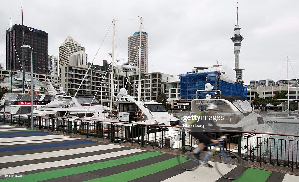 A cyclist rides past boats moored at the Viaduct Basin as buildings stand in the central business district in Auckland New Zealand on Tuesday March...