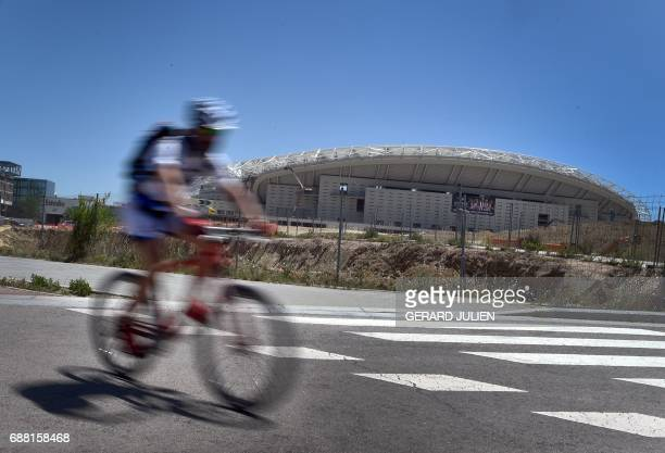 A cyclist rides past construction works at the Wanda Metropolitano Stadium in Madrid on May 24 the new stadium of Club Atletico de Madrid that is to...