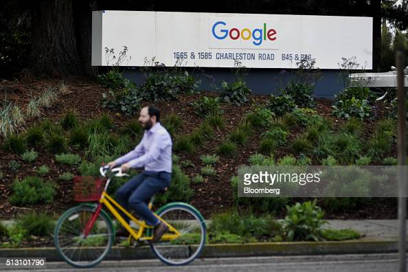 A cyclist rides past Google Inc signage near the entrance to the Googleplex headquarters in Mountain View California US on Thursday Feb 18 2016...