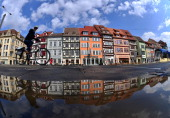 A cyclist rides past houses on Cathedral Square on April 11 2013 in Erfurt Germany AFP PHOTO / MARTIN SCHUTT /GERMANY OUT