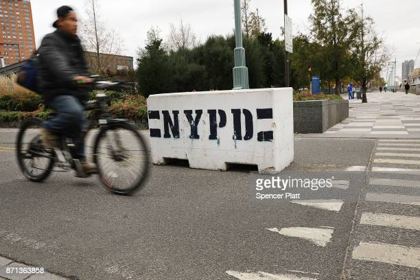A cyclist rides past new police barriers near the location where terrorist Sayfullo Saipov entered a Manhattan bike path and went on a rampage with a...
