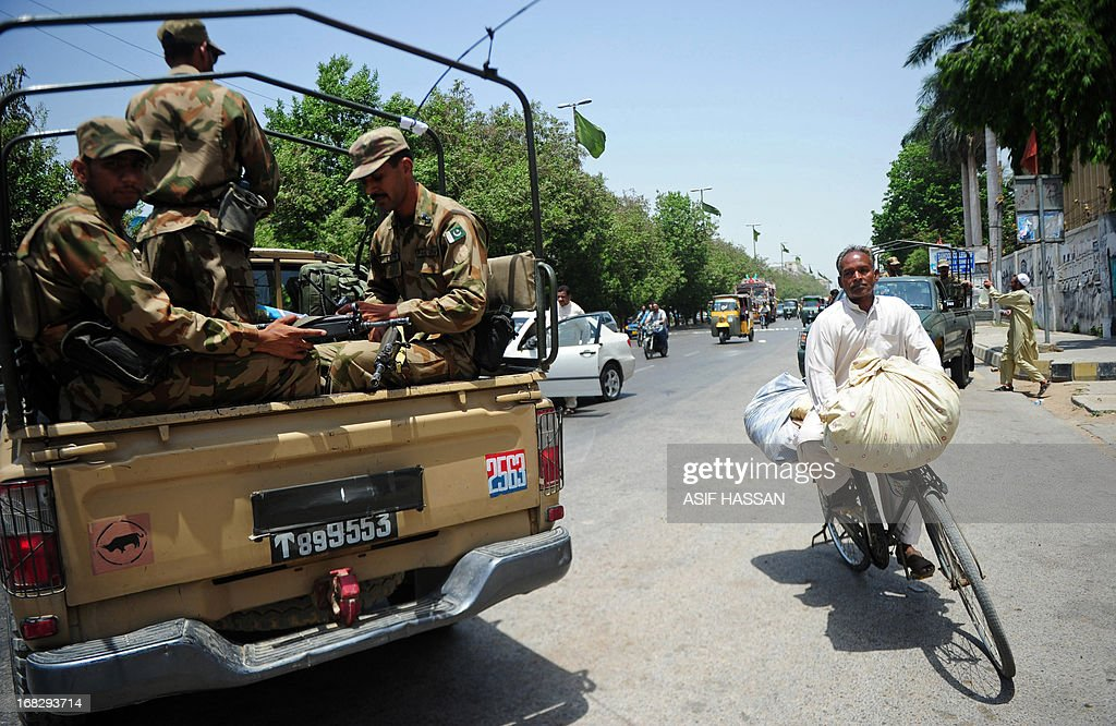 A cyclist rides past Pakistan soldiers as they patrol a street in Karachi on May 8, 2013. Pakistan goes to the polls on May 11 to elect lawmakers to the lower house of parliament and four provincial assemblies. It is the first time that a civilian government has completed a full term and handed over power through the ballot box in Pakistan's 66-year history. AFP PHOTO/ ASIF HASSAN