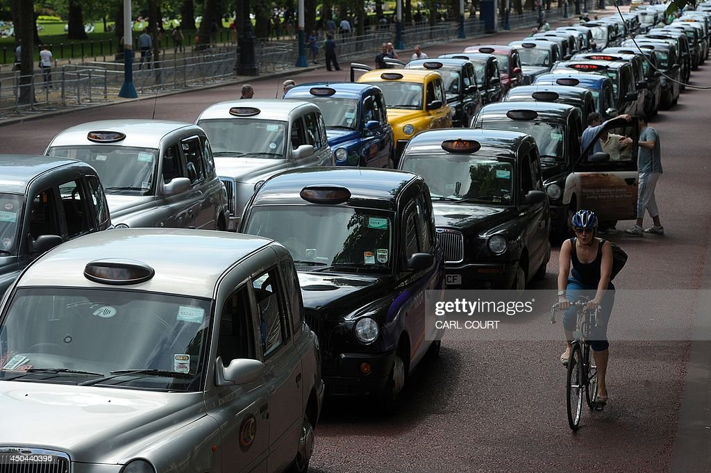 A cyclist rides past parked taxis during a protest by London black cab drivers against a new private taxi service 'Uber', a mobile phone app, on the Mall leading to Buckingham Palace in central London on June 11, 2014. Taxi drivers brought parts of London, Paris and other European cities to a standstill on June 11 as they protested against new private cab apps such as Uber which have shaken up the industry. Thousands of London's iconic black cabs, many of them beeping their horns, filled the roads around Buckingham Palace, Trafalgar Square and the Houses of Parliament to the exclusion of any other vehicles.