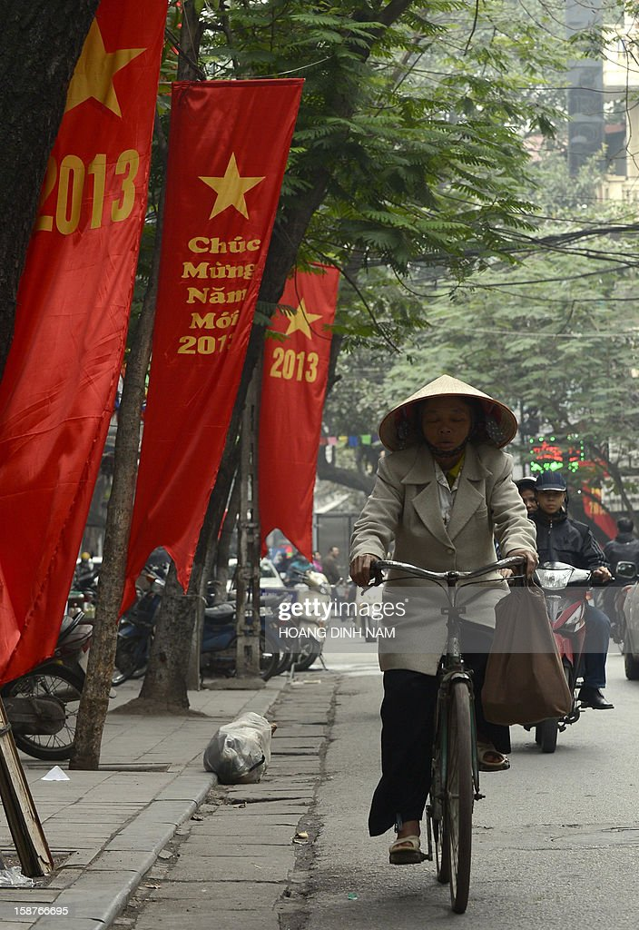 A cyclist rides past red banners marking the 2013 new year in downtown Hanoi on December 28, 2012. Vietnam's economic growth slowed to the weakest pace in 13 years in 2012, according to published official statistics, piling more pressure on the country's rulers. Gross domestic product grew by 5.03 percent this year while inflation slowed to 6.8 percent in December year-on year from 7.08 percent in November. AFP PHOTO/HOANG DINH Nam