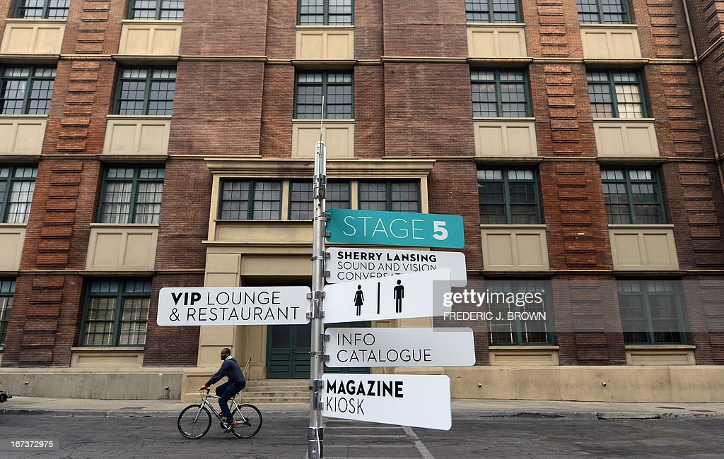 A cyclist rides past street signs in a re-created old New York neighborhood on site at the Paramount Pictures Studios in Los Angeles, as preparations are underway ahead of the opening of Paris Photo in Los Angeles on April 24, 2013 in California. The prestigious art fair dedicated to historical and contemporary photography which began in Paris in 1996 is taking place at the Paramount Pictures Studios in Los Angeles on April 26-28. AFP PHOTO/Frederic J. BROWN