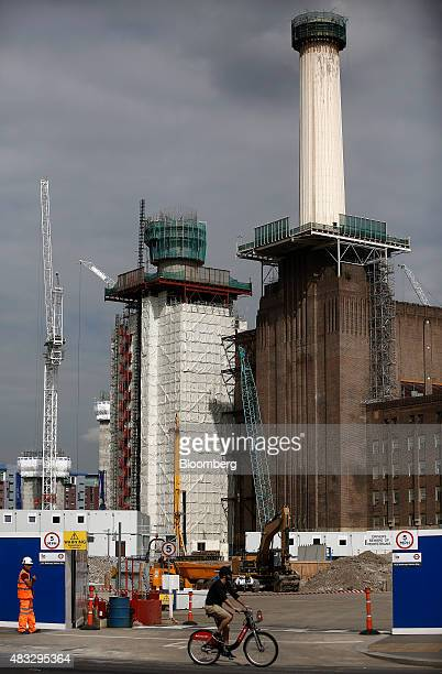 A cyclist rides past the Battersea power station residential and retail development in London UK on Friday Aug 7 2015 Demand for London homes under...