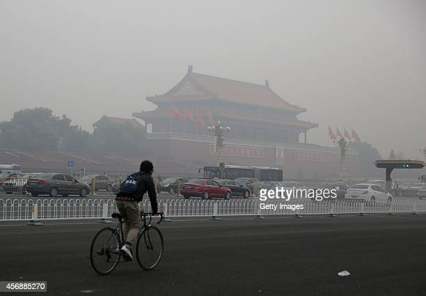 A cyclist rides past the Tiananmen Rostrum as heavy smog engulfs the city on October 9 2014 in Beijing China China's National Meteorological Center...