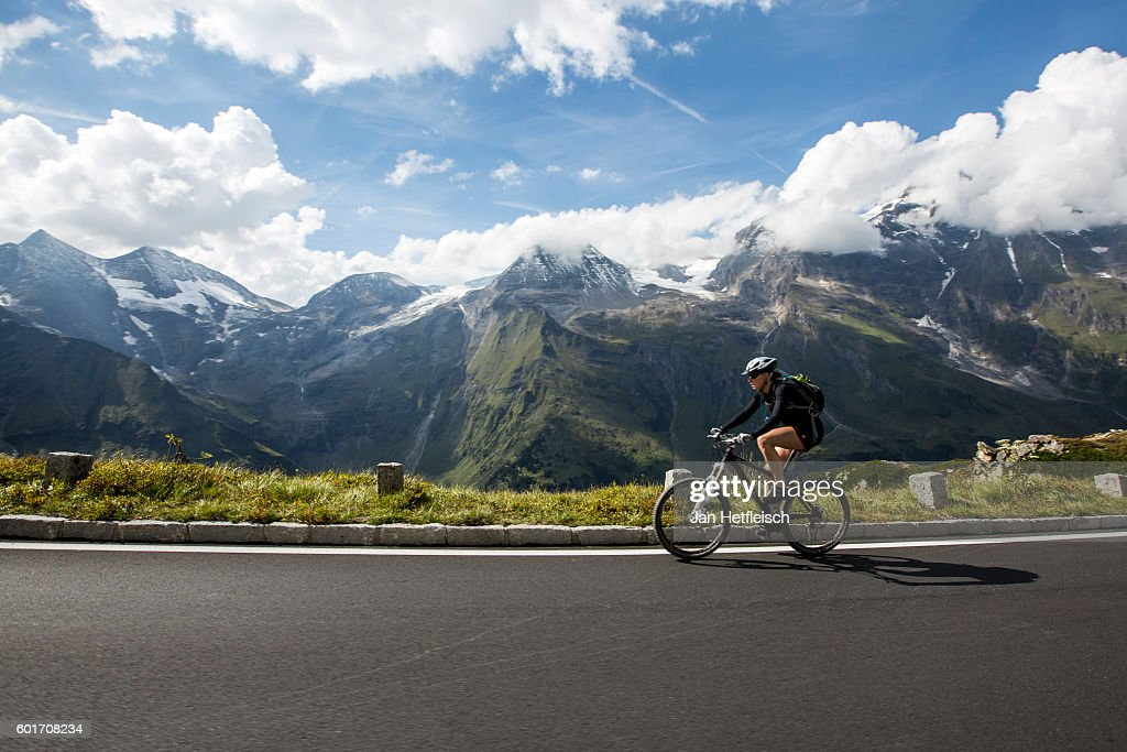 A cyclist rides the Grossglockner high alpine road on September 09, near Zell am See, Austria. The Grossglockner high alpine road is the highest mountain pass road in Austria. It connects Bruck in the state of Salzburg with Heiligenblut in Carinthia. The road is named after the Grossglockner, Austria's highest mountain (3798 m). The road was build from 1930 to 1935. Humans have been crossing the Alps on a path that mainly follows the modern road for more than 3500 years. Celts, Romans, sumpters, gold diggers and galley slaves got past this strenuous and dangerous path.