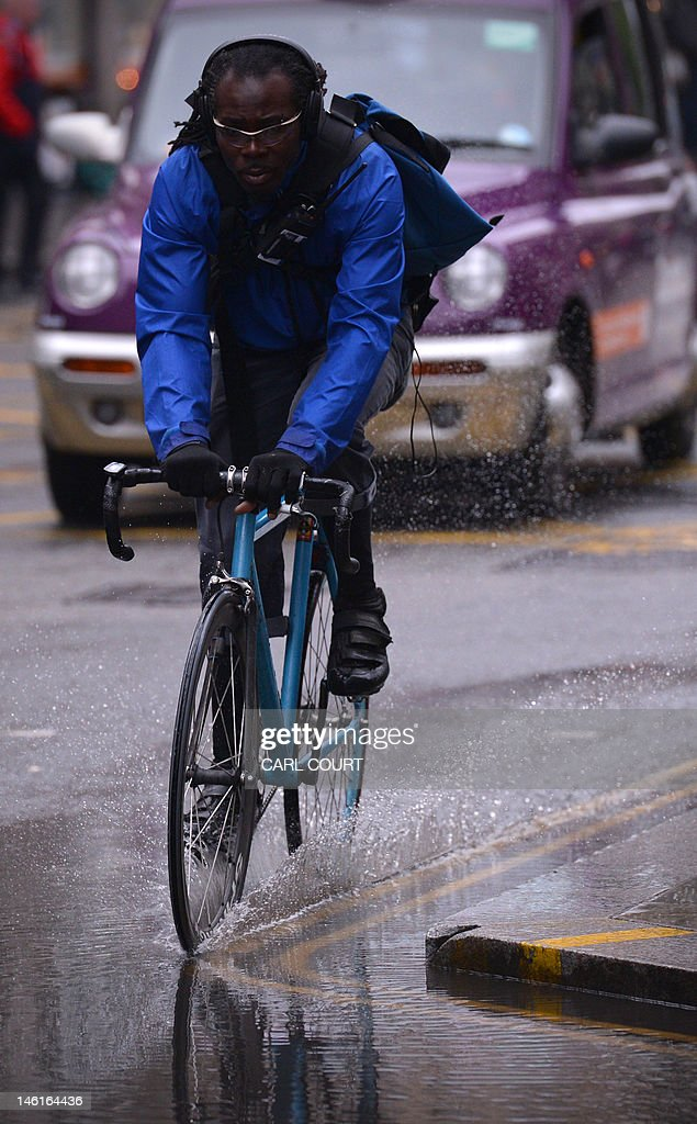 A cyclist rides through a puddle left by persistent rain in central London on June 11, 2012. Persistent rainfall over much of southern England and the midlands has lead to the risk of flooding with the Met office issuing a severe weather warning.