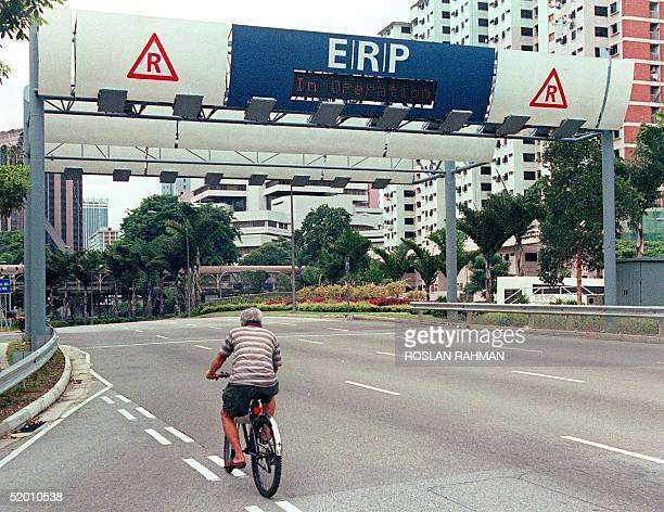 A cyclist rides towards an Electronic Road Pricing gantry into Singapore's central business district Communication Minister Mah Bow Tan said travel...