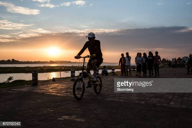 A cyclist rides while pedestrians walk on a promenade along the Mekong river in Vientiane Laos on Thursday Nov 2 2017 Located in the Mekong region...