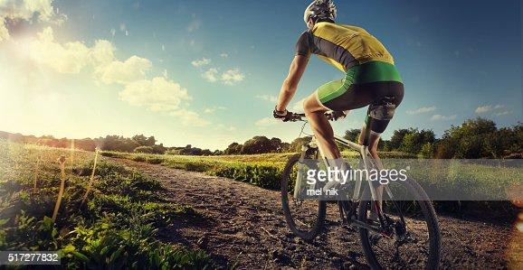 Ciclista andar de bicicleta ao pôr do sol sobre o ofroad : Foto de stock