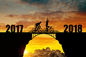 Cyclist riding across the bridge at sunset. Forward to the New Year 2018.