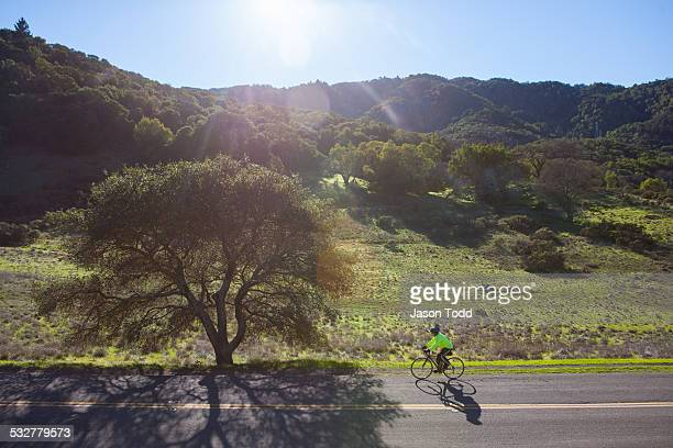 Cyclist riding along scenic road