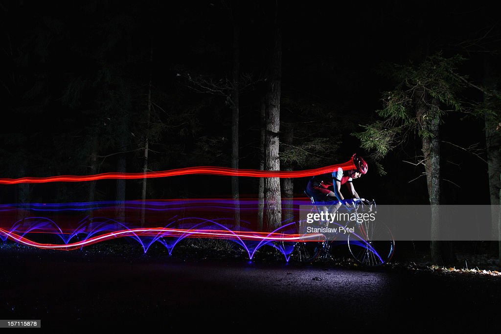cyclist riding at night leaving streaks of light : Stock Photo