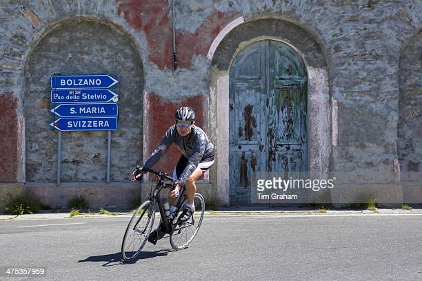 Cyclist riding British Scott bike passes signpost on The Stelvio Pass Passo dello Stelvio Stilfser Joch in Northern Italy