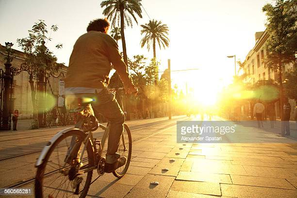 Cyclist riding into sunset in Sevilla, Spain